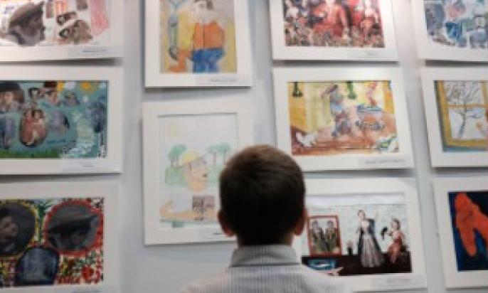 Мальчик смотрит на нарисованые картины.