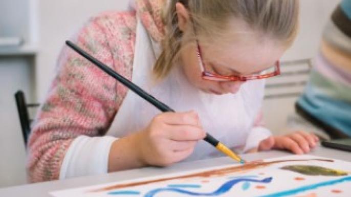 Девочка в очках рисует картину кисточкой.